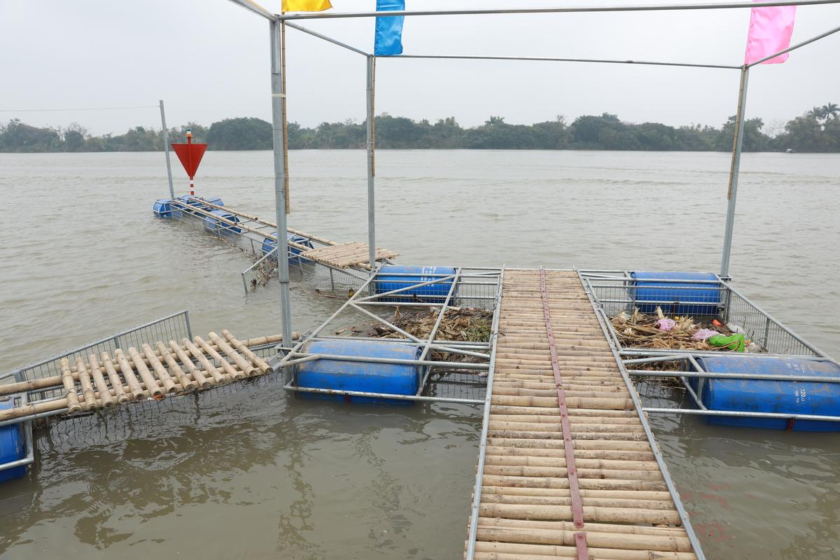 A locally designed, inexpensive trash trap has been installed along Vietnam's Song Hong River to remove floating debris such as plastic waste