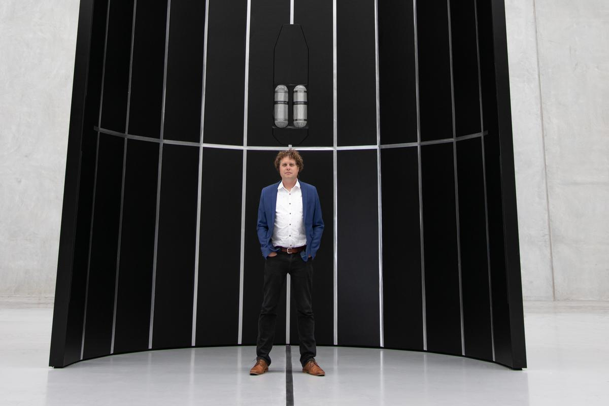 Rocket Lab CEO Peter Beck stands in front of the payload fairing for the company's Neutron rocket