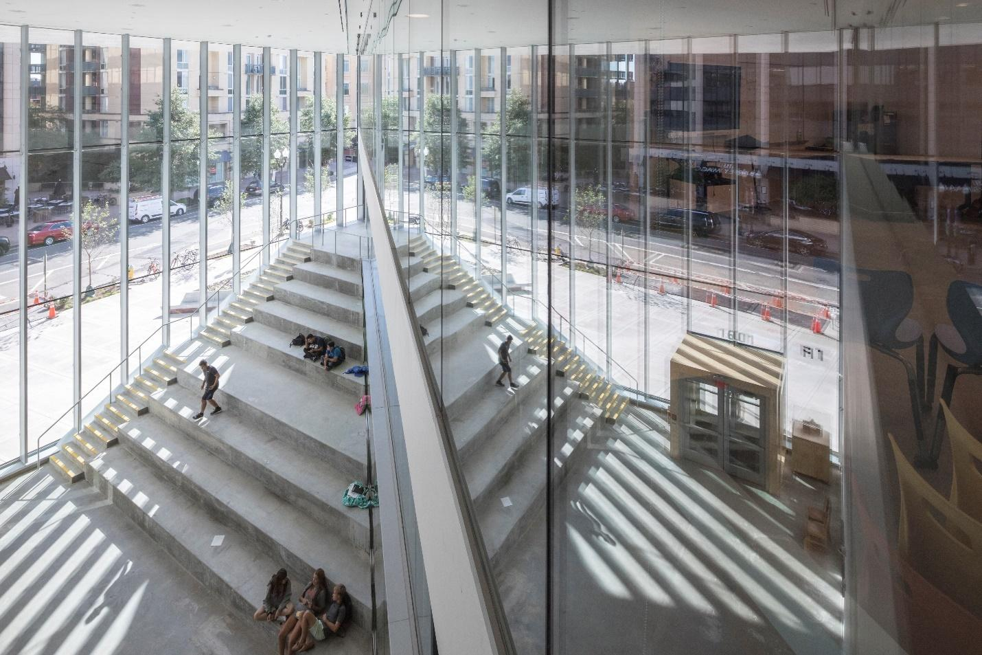 """""""Underneath the canopy of fanning classrooms, a giant cave holds spaces for all the communal spaces – the theatre, the sports hall, library and canteen – creating a multitude of spaces where students can linger for fun or for study – on their own or in groups,"""" says Bjarke Ingels"""
