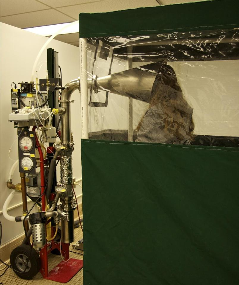 A study participant sits in the Gesundheit II machine, which is used to capture and analyze influenza virus in exhaled breath
