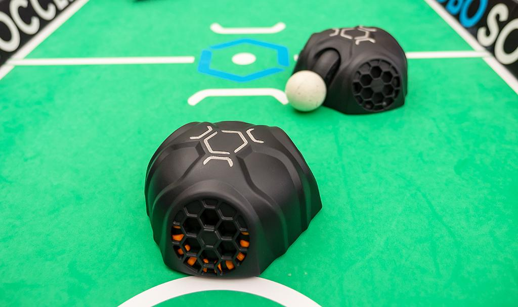 "The robots can grab the ball, or they can ""dribble"" it simply by pushing it along"