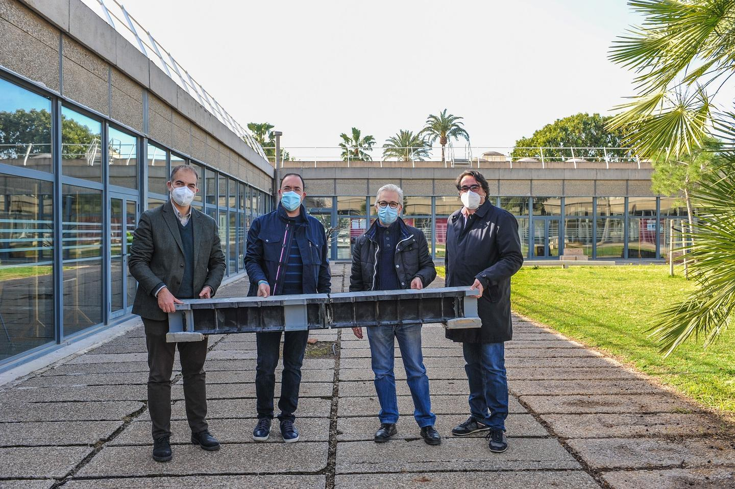 The Polytechnic University of Valencia research team with one of its 3D-printed beams