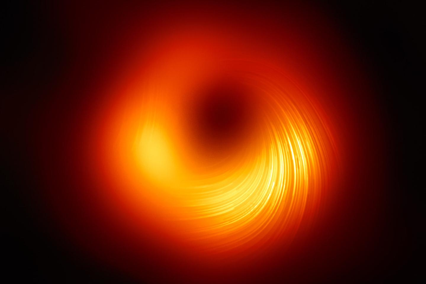 The Event Horizon Telescope (EHT) Collaboration's updated image of the black hole in the galaxy M87 – the white lines represent the polarization of light in the ring, which can reveal new clues about the magnetic field in this extreme environment