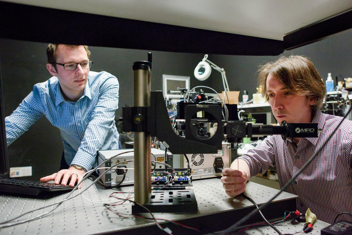 Stanford researchers David Lindell (left) and Matt O'Toole work on a laser-based system that can detect hidden objects around corners