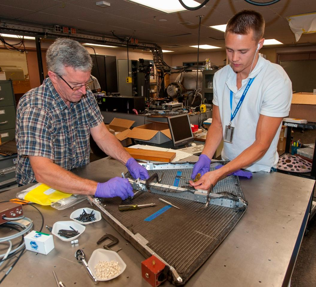 Paul Wercinski, ADEPT project manager and Cole Kazemba, ADEPT system engineer, attach the woven carbon fabric skin to the ribs of an early version of ADEPT in the assembly lab at Ames