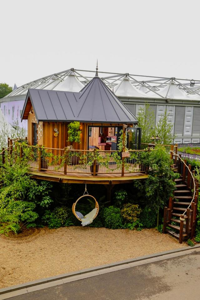 The treehouse features two spiral staircases, which lead to the entrance of the treehouse and the large outdoor deck