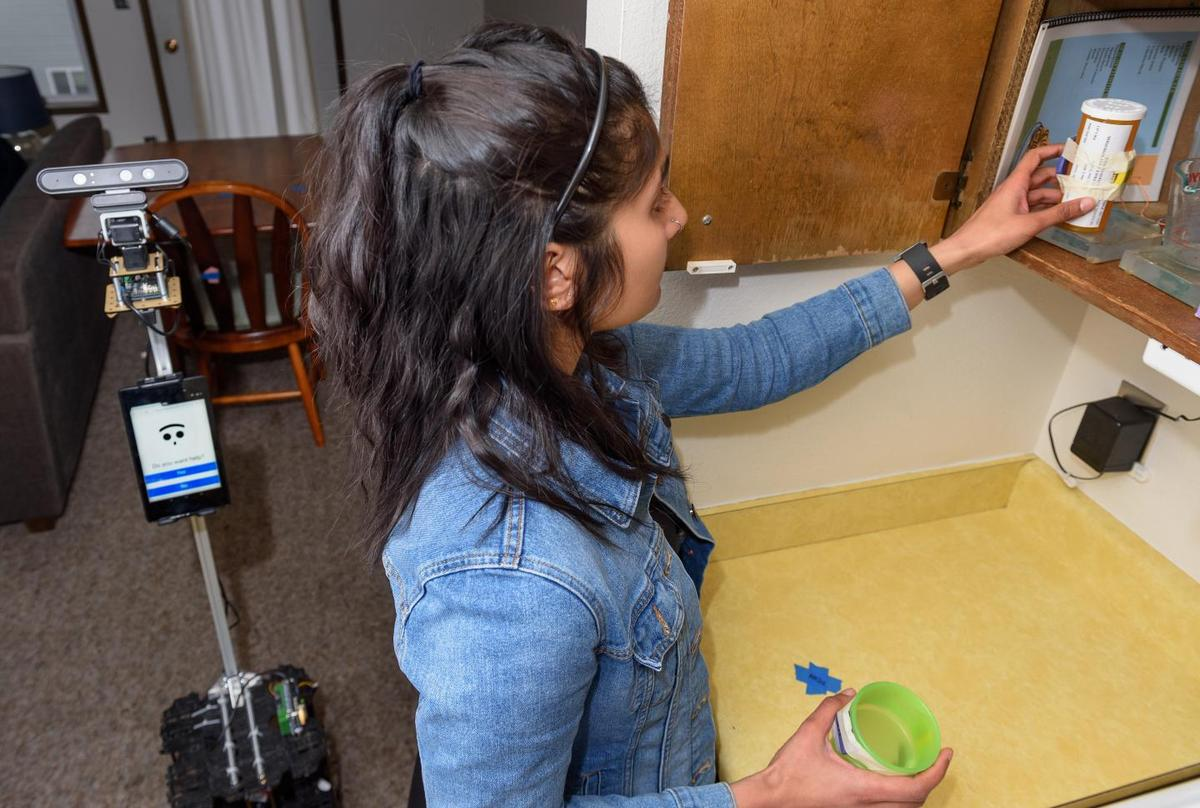 The robot assists master's student Nisha Raghunath in a medication-taking task