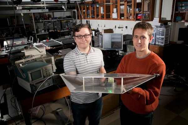 Duke engineering students Alexander Katko (left) and Allen Hawkes show a waveguide containing a single power-harvesting metamaterial cell, which provides enough energy to power the attached green LED