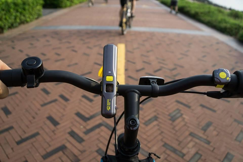 "The RidingToo RT1 consists of two parts: a main ""host"" unit that is mounted on the handlebars or carried on the rider's body, along with a bar-mounted Bluetooth remote"