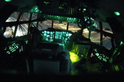 In the shadows of their C-130 Hercules' flight deck, (left to right) pilot Maj. Mike Wilson, flight engineer Senior Master Sgt. Ernie Leyba and co-pilot Capt. Tim Pemberton approach for a landing at Balad Air Base. (U.S. Air Force photo by Master Sgt. Lan