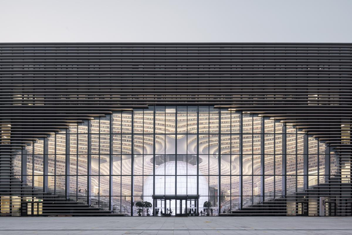 The undulating shelves blur the outside and inside of the Tianjin Binhai Library