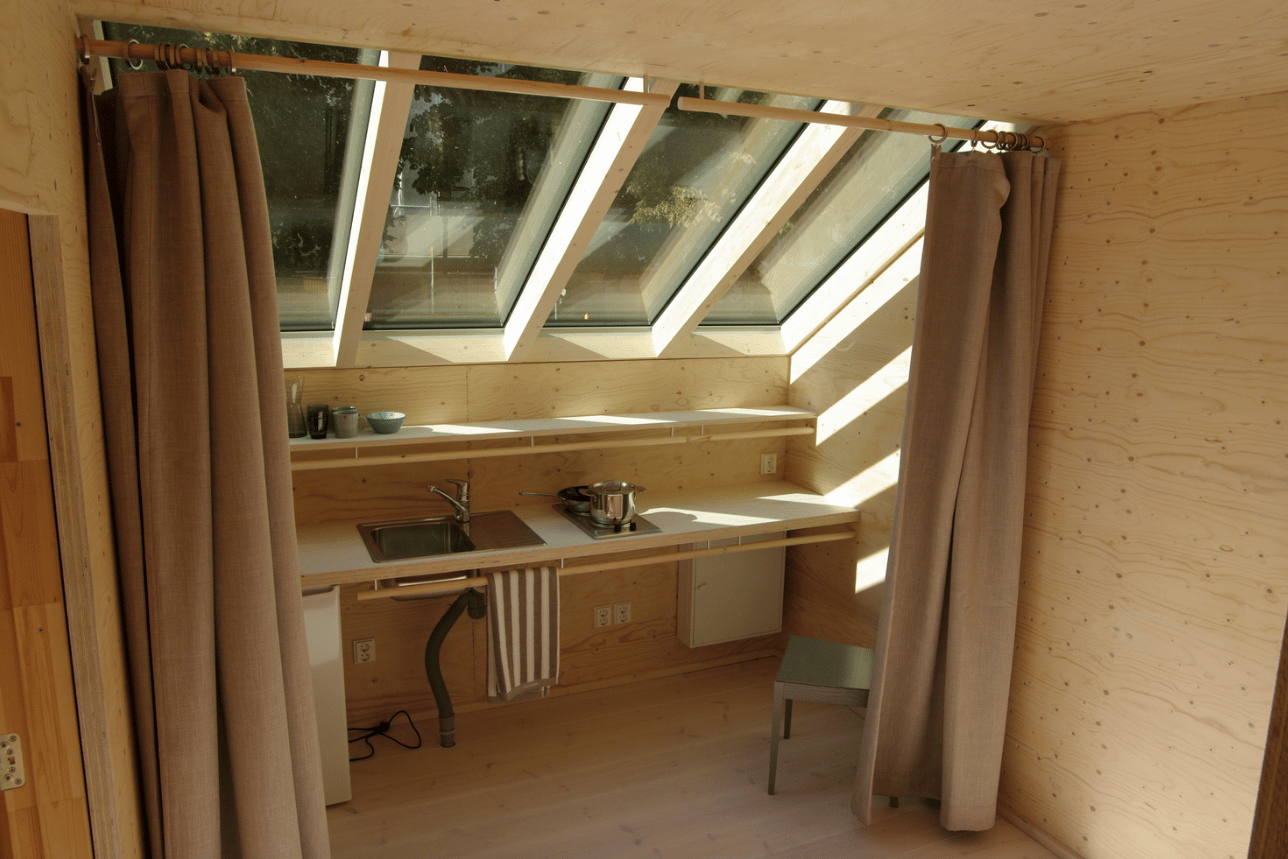 The interior includes a dining area, kitchen, bathroom, and bedroom over its three floors