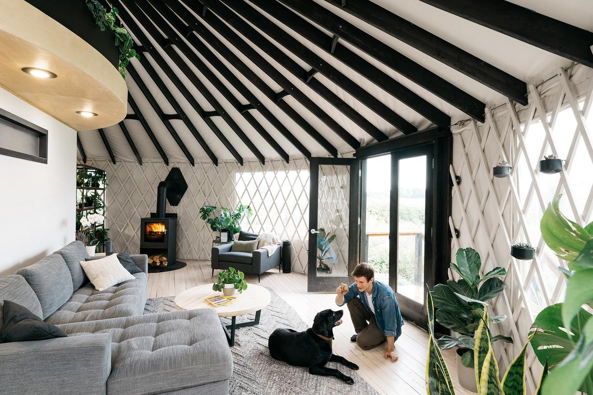 The yurt home features wooden floorboards and open lounge area