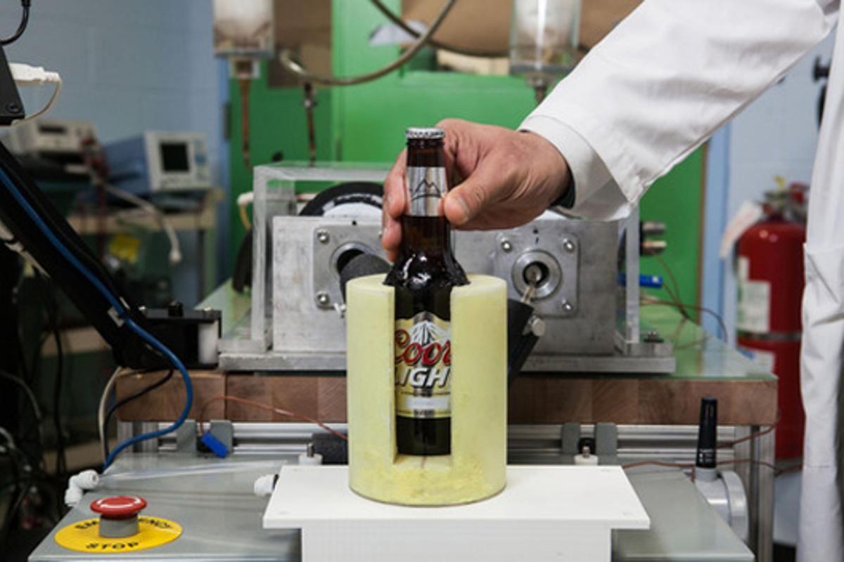 A bottle of beer is cooled using the new magnetic refrigeration system developed by GE
