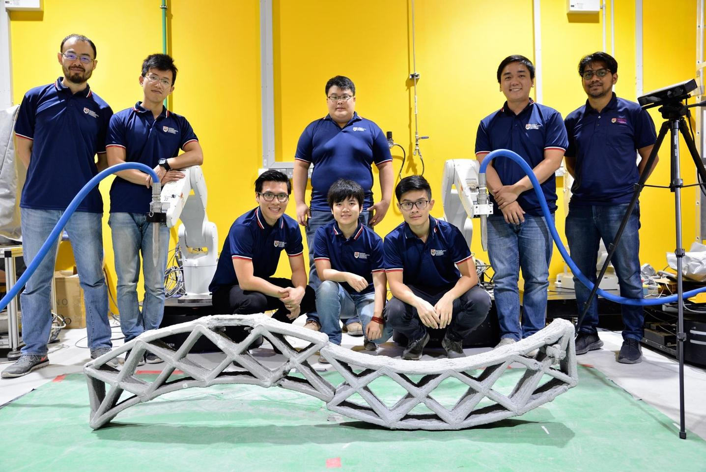 The NTU team with the two robots and the structure that they built