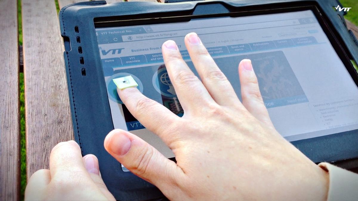 This person uses a fingernail-shaped chip to transfer data between a tablet and a smartphone with just a touch.
