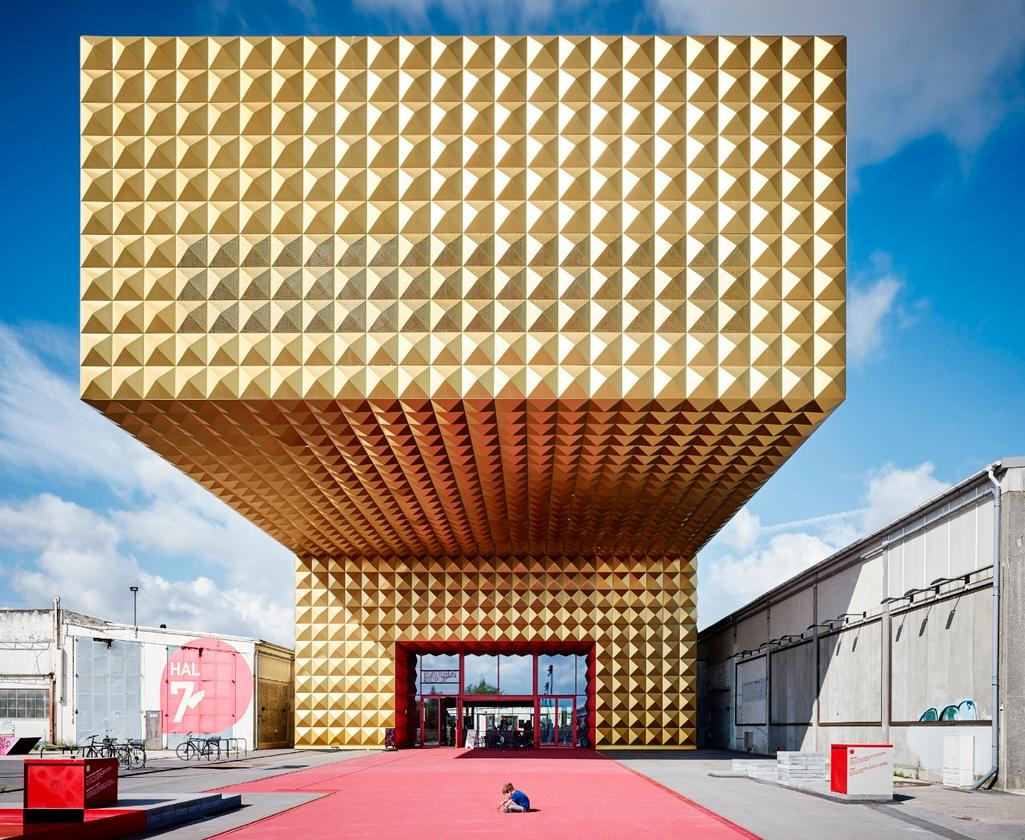 "Ragnarock - Museum of Pop, Rock & Youth Culture, in Roskilde, Denmark, by Michael Moser, is an AIA|LA APA Honor award recipient. ""This is a traditional, classical, iconic building – and if not the building, certainly the image of it,"" says AIA's jury. ""The huge, gold structure cantilevered out looks almost dangerously powerful, as if it's going to crush a small child who is kneeling beneath it"""