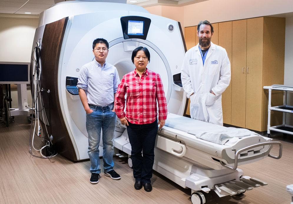 The researchers, in front of an MRI machine