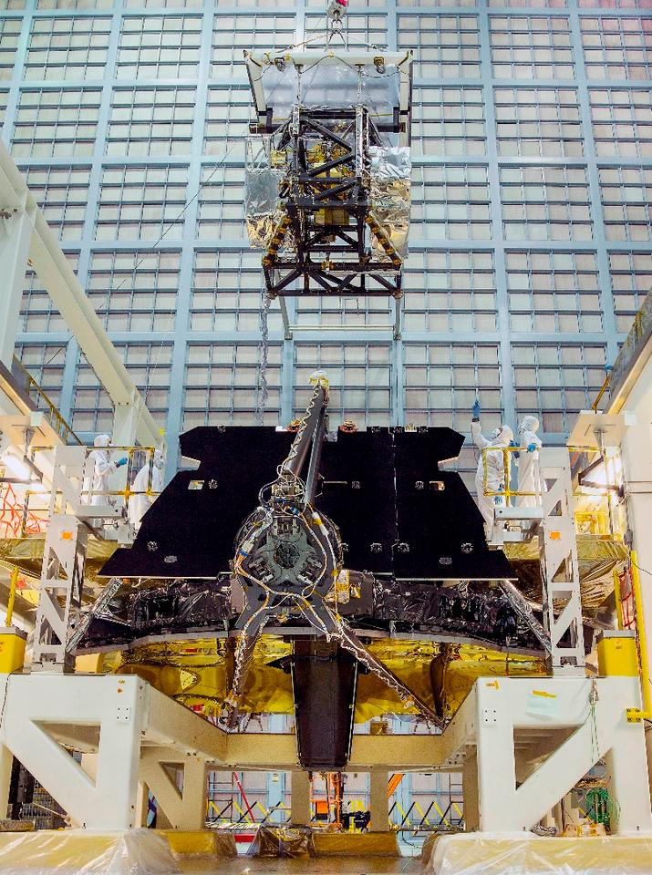 The ISIM unit is carefully lowered onto the back of the JWST, which is lying face down in the world's largest clean room located in Greenbelt, Maryland