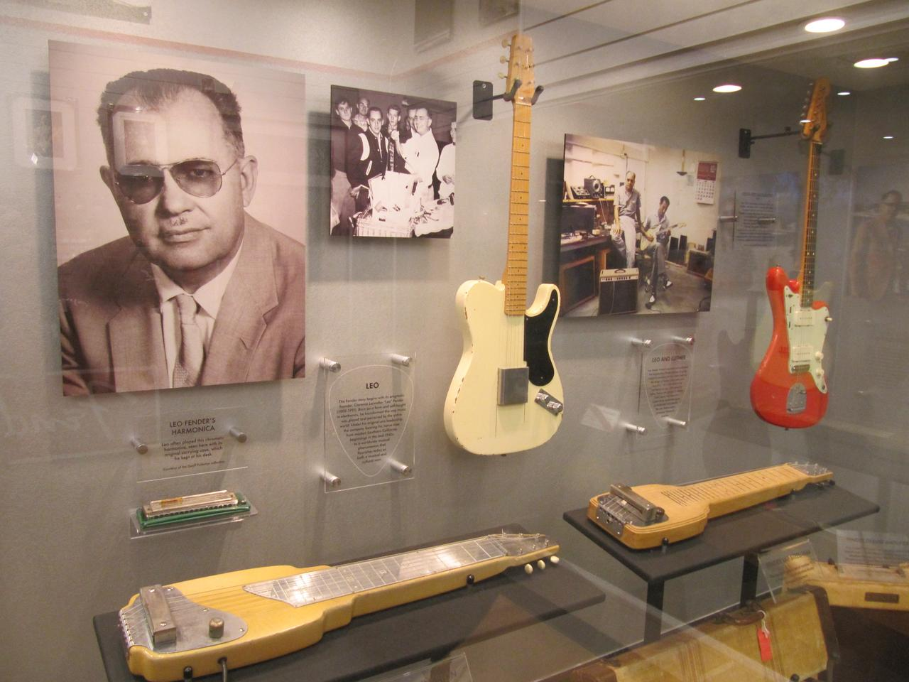 Photo of Leo Fender, along with some early guitar models on show at the Fender Guitar Factory Museum
