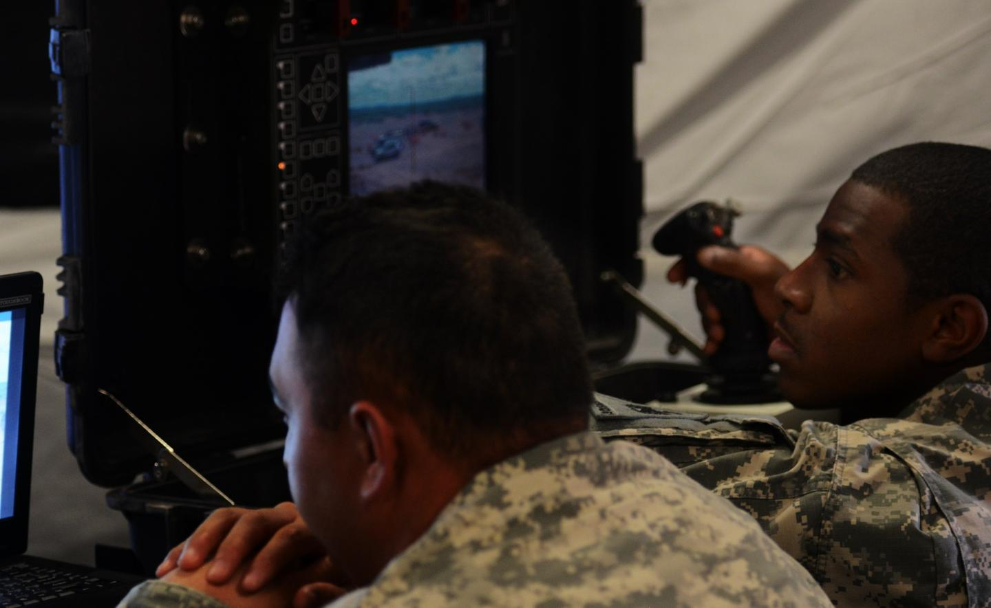 Soldiers inside their tactical operations center remotely control multiple weapons systems on the perimeter