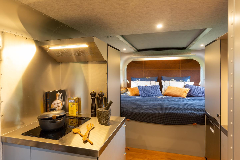 Вътрешната кухня включва печка с три горелки, мивка и хладилник/фризер
