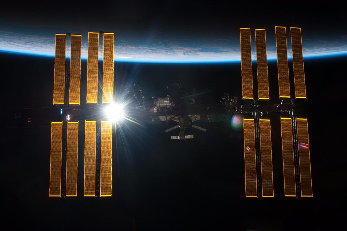 The Sun shining through the solar panels of the ISS