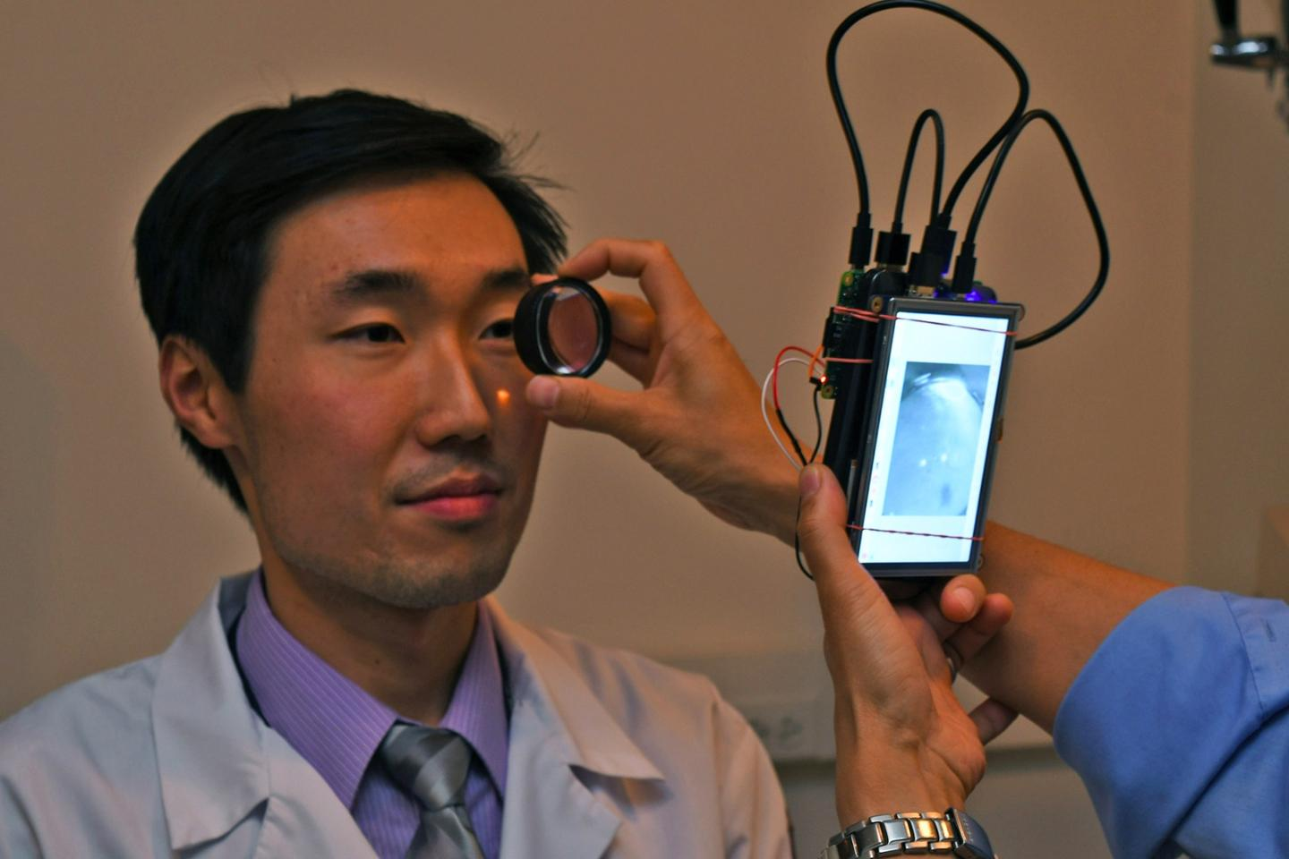 Dr. Bailey Shen has his retina imaged using the prototype camera