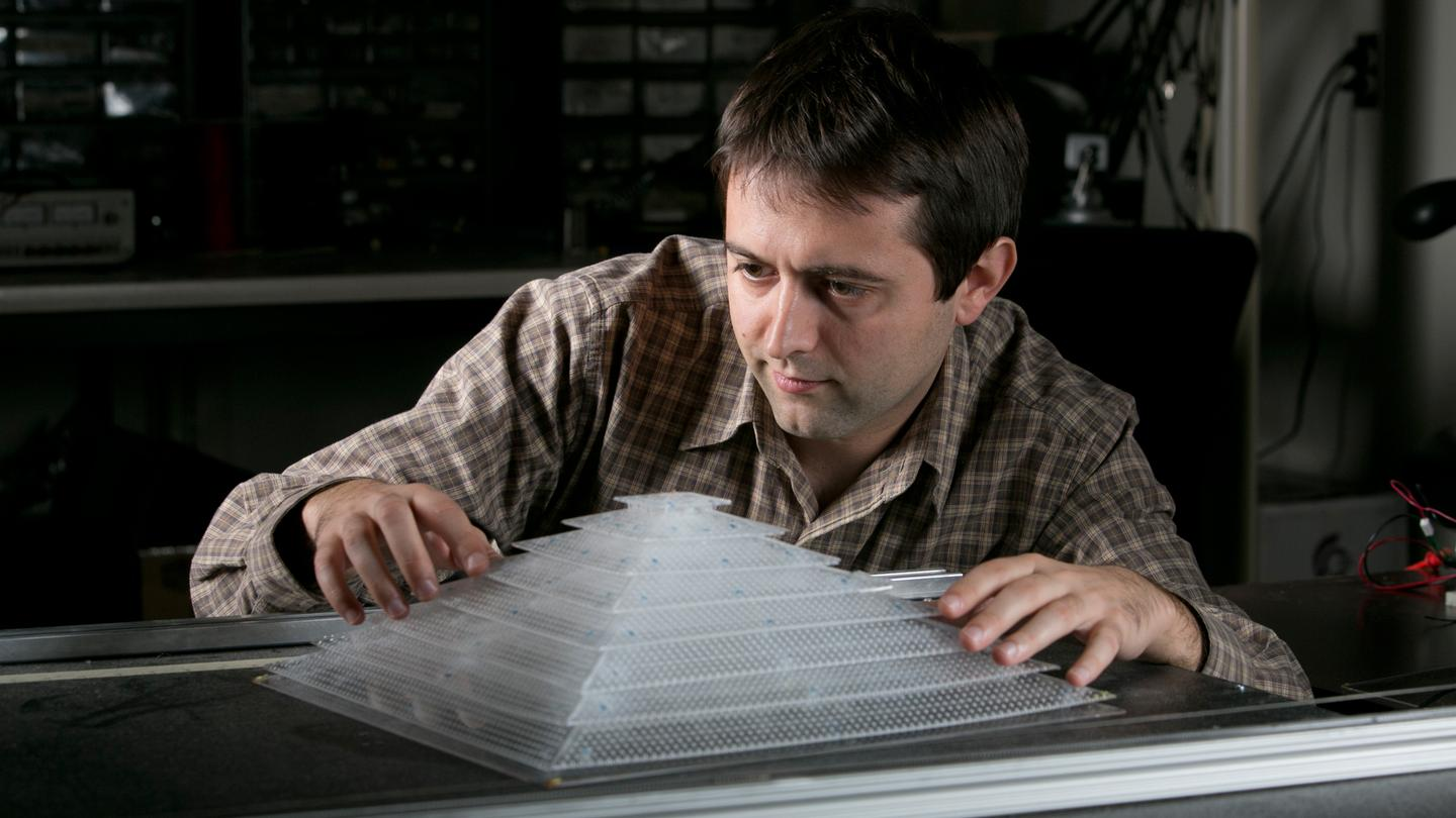 Research scientist Bogdan Popa with a 3D acoustic cloaking device constructed with components created in a 3-D printer (Photo: Duke Photography)