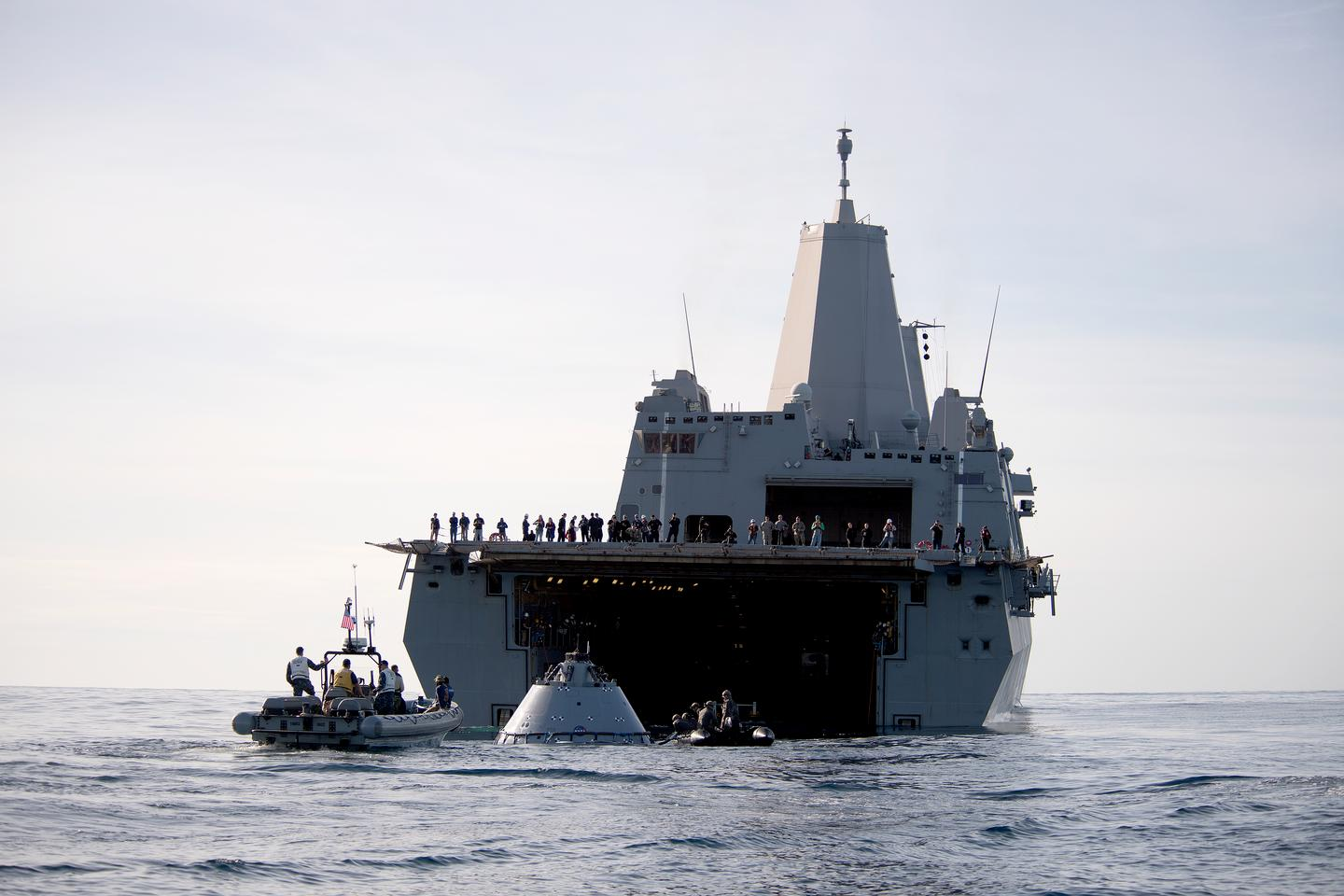 The Orion test capsule being guided into the well of USS Anchorage
