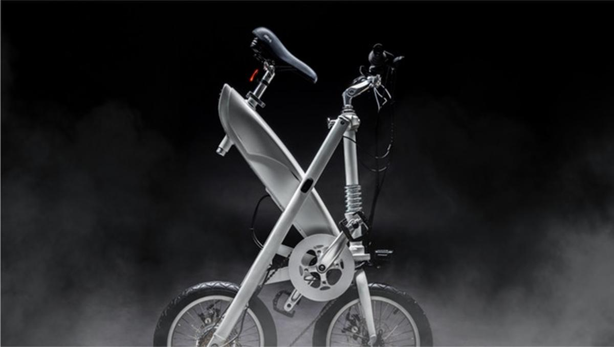 The folding point is at the center of the frame, with the rider pulling on a central knob and lifting up to fold