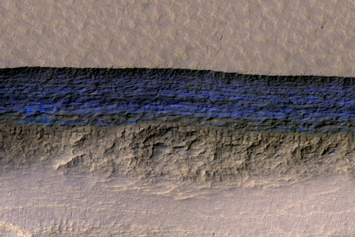 The blue section (artificially colored) represents the exposed face of an underground ice sheet on Mars, at a scale of about 500 m (1,650 ft) wide