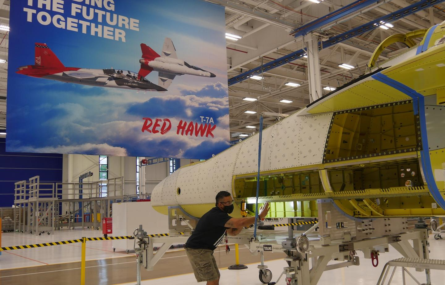Boeing T-7A Red Hawk aircraft mechanic Will Helton examines the first spliced advanced trainer