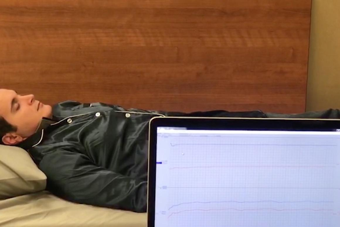 A volunteer helps test the Phyjama – their sleep data is visible on the computer screen