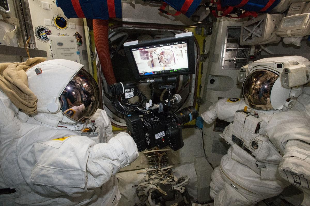 The RED Epic Dragon camera floating between two spacesuits aboard the ISS