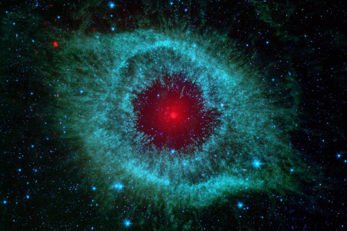 One of the most eye-catching shots Spitzer ever took, showing the Helix Nebula, a cloud of dust two light-years wide, with the bright red center hiding a dying star shrouded in its own disk of debris
