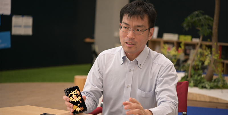 Shukichi Tanaka, one of the NEC researchers with the new bioplastic used in a smartphone